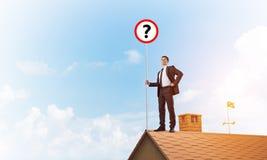Zakenman op het dak die van het baksteenhuis banner met vraagteken tonen Gemengde media Royalty-vrije Stock Foto