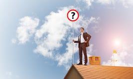 Zakenman op het dak die van het baksteenhuis banner met vraagteken tonen Gemengde media Royalty-vrije Stock Afbeelding