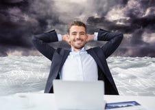 Zakenman op laptop in overzees van documenten onder donkere hemelwolken Stock Foto