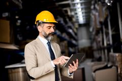 Zakenman op middelbare leeftijd met digitale tablet in fabriek royalty-vrije stock fotografie