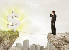 Zakenman op rotsberg met een dollarteken Stock Foto