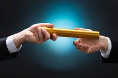 Zakenman Passing Relay Baton aan Collega stock afbeelding
