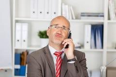 Zakenman Puckering Lips While die Draadloze Telefoon met behulp van Stock Fotografie