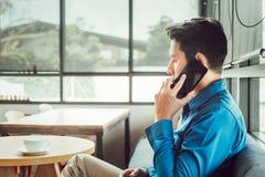 Zakenman raadplegende partner telefonisch terwijl het zitten in de koffiewinkel royalty-vrije stock afbeeldingen