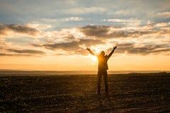 Zakenman Raising Arms voor Succes bij het Gebied op zonsondergang royalty-vrije stock foto's