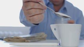Zakenman Relax Preparing een Hete Koffie die Wat Suiker met een Theelepeltje toevoegt stock afbeeldingen