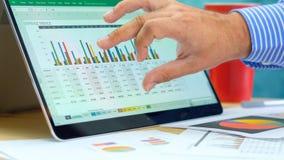 Zakenman richtende en uitbreidende grafieken op moderne laptop van het aanrakingsscherm stock foto