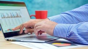 Zakenman richtende en uitbreidende grafieken op moderne laptop van het aanrakingsscherm stock afbeeldingen