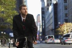 Zakenman Riding Bicycle While die weg kijken Royalty-vrije Stock Afbeeldingen