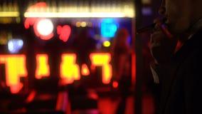 Zakenman rokende sigaar in elitebar, de atmosfeer van de nachtclub, vrouwen het dansen stock footage