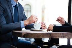 Zakenman ` s en onderneemster` s handen met koffie royalty-vrije stock afbeeldingen