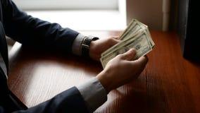 Zakenman` s handen die honderd dollarsrekeningen tellen bij een lijst handen met horloge en dollars op houten lijst Het concept v stock video