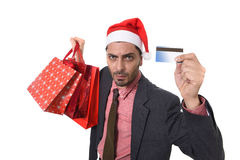 Zakenman in Santa Claus Christmas-hoedenholding die zakken en creditcard in ongerust gemaakt soppen en spanning Royalty-vrije Stock Fotografie