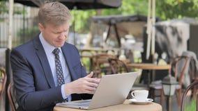 Zakenman in Schok door Mislukking op Laptop, Openluchtkoffie stock footage
