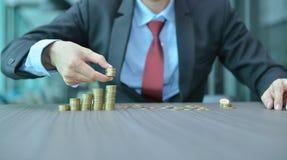 Zakenman Stacking Coins in Stijgende Orde bij bureau stock foto's