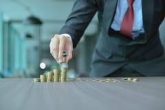 Zakenman Stacking Coins in Stijgende Orde bij bureau royalty-vrije stock afbeeldingen