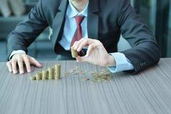 Zakenman Stacking Coins in Stijgende Orde bij bureau stock foto