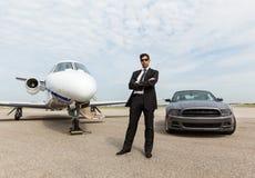 Zakenman Standing By Car en Privé Jet At Royalty-vrije Stock Foto