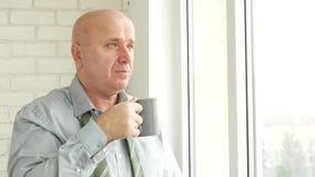 Zakenman Stay op Venster Peinzend Drinken een Kop thee stock videobeelden