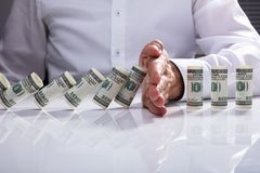 Zakenman Stopping Falling Rolled op Bankbiljetten royalty-vrije stock afbeelding