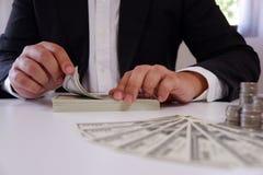 Zakenman tellend geld met muntstukken en geld over het bureau stock foto