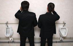 Zakenman twee met mobiele telefoons in een WC royalty-vrije stock foto