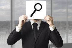 Zakenman verbergend gezicht achter meer magnifier teken loup Royalty-vrije Stock Fotografie