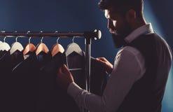 Zakenman in vest, rij van kostuums in winkel Modieuze mens in een doekjasje Het is in de toonzaal, die op kleren proberen stock fotografie