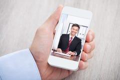 Zakenman videoconfereren met collega bij bureau Stock Foto