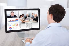Zakenman videoconfereren met collega's op PC bij bureau stock afbeelding