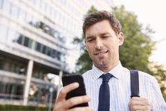 Zakenman Walking To Work in Stad die Mobiele Telefoon bekijken stock afbeelding
