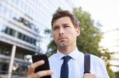 Zakenman Walking To Work in Stad die Mobiele Telefoon bekijken stock fotografie