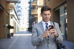 Zakenman Walking To Work in Stad die Mobiele Telefoon bekijken stock foto