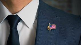 Zakenman Walking Towards Camera met de speld-Verenigde Staten van het Land Vlag van Amerika stock video