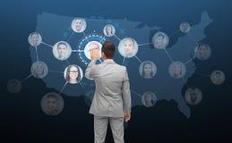 Zakenman wat betreft het virtuele scherm met contacten Stock Afbeelding