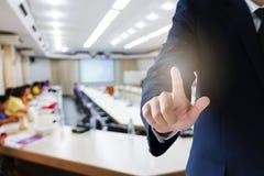 Zakenman wat betreft het visuele scherm met de vage achtergrond van de conferentieruimte Royalty-vrije Stock Fotografie