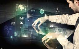 Zakenman wat betreft interactief modern bureau met technologieico Stock Fotografie