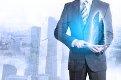 Zakenman wat betreft tablet met 3d stadsmodel Stock Afbeelding