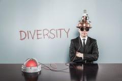Zakenman Wearing Helmet Sitting door Diversiteitstekst op Gray Wall stock fotografie