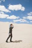 Zakenman in woestijn met fles Stock Fotografie