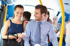 Zakenman And Woman Looking bij Mobiele Telefoon op Bus Royalty-vrije Stock Fotografie