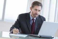 Zakenman Writing Notes While die Laptop met behulp van bij Bureau royalty-vrije stock afbeeldingen