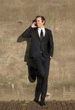 Zakenman in zwart kostuum die op mobiele telefoon in openlucht spreken Stock Afbeelding