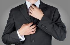 Zakenman in zwarte kostuumband zijn stropdas Royalty-vrije Stock Foto