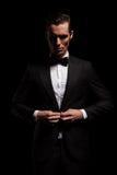 Zakenman in zwarte toxedo met bowtie het stellen in donkere studio Royalty-vrije Stock Afbeelding