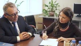 Zakenmanadviezen om tot vennootschap aan hogere dame op de vergadering in bureau te maken stock footage