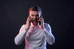Zakenmanbesprekingen op twee telefoons en schreeuwen van overspanning en stock afbeelding