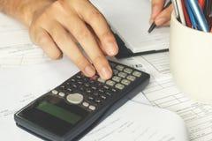 Zakenmanhand die een calculator gebruiken om de aantallen te berekenen Boekhouding Stock Fotografie