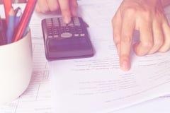 Zakenmanhand die een calculator gebruiken om de aantallen te berekenen Boekhouding Royalty-vrije Stock Foto