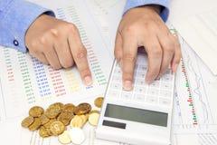 Zakenmanhand die een calculator op bureau gebruiken stock foto's